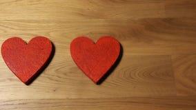 Manos femeninas hermosas que ponen tres formas rojas del corazón en la tabla de madera Familia, cuidado, conceptos de la cardiolo almacen de metraje de vídeo