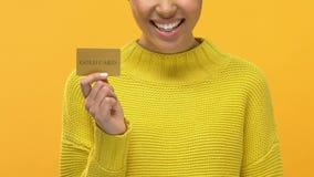 Manos femeninas jovenes alegres de la tarjeta de crédito del oro que se sostienen, venta que hace compras, consumerismo almacen de video