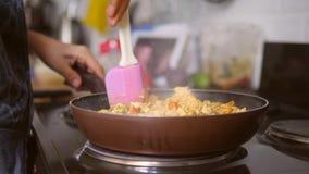 Manos femeninas jovenes que cocinan la tortilla del queso de soja de Scrabled del vegano en la cocina 4K, a cámara lenta almacen de video