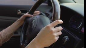 Manos femeninas jovenes que sostienen con confianza el volante del coche, conducción de la mujer metrajes