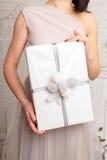 manos femeninas jovenes que sostienen el regalo, mujer que da la caja, el concepto de la Navidad y del Año Nuevo Imagenes de archivo