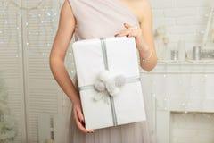manos femeninas jovenes que sostienen el regalo, mujer que da la caja, el concepto de la Navidad y del Año Nuevo Imagen de archivo