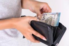 Manos femeninas jovenes que sostienen la cartera negra con el dinero euro y la paga imagen de archivo libre de regalías