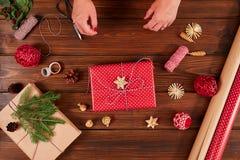 Manos femeninas que adornan las cajas rojas del regalo para el día de fiesta de la Navidad Las manos se cierran para arriba imágenes de archivo libres de regalías
