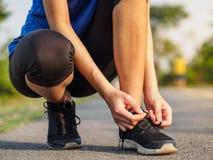 Manos femeninas que atan el cordón en las zapatillas deportivas antes de práctica ru imagen de archivo