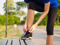 Manos femeninas que atan el cordón en las zapatillas deportivas antes de práctica ru fotografía de archivo