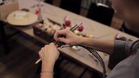 Manos femeninas que atan encima de las barras de madera con un alambre para la guirnalda de la Navidad