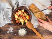 Manos femeninas que cortan el pan en el fondo de la tabla Aún vida rural de patatas cocidas con la carne en un de cerámica Imagen de archivo