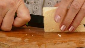 Manos femeninas que cortan el queso en la tabla de cortar de madera metrajes