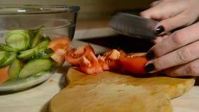Manos femeninas que cortan el tomate metrajes