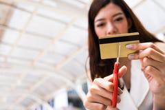 Manos femeninas que cortan la tarjeta de crédito con las tijeras foto de archivo