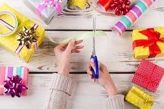 Manos femeninas que cortan una cinta Imagen de archivo libre de regalías