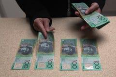 Manos femeninas que cuentan al australiano 100 dólares de cuentas Imagen de archivo libre de regalías
