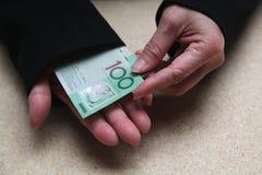 Manos femeninas que cuentan al australiano 100 dólares de cuentas Imagen de archivo