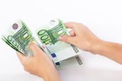 Manos femeninas que cuentan 100 billetes de banco euro Foto de archivo