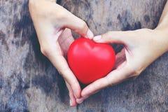 Manos femeninas que dan el corazón rojo Tono del vintage Foto de archivo libre de regalías