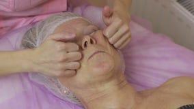 Manos femeninas que dan masajes a la cara mayor del ` s de la mujer almacen de video