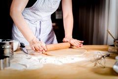 Manos femeninas que desarrollan la pasta en la tabla de cocina, cierre para arriba Imágenes de archivo libres de regalías