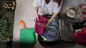 Manos femeninas que embalan la ropa en bolso del viaje almacen de video