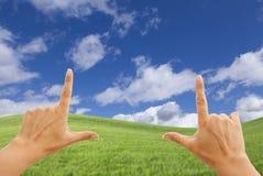 Manos femeninas que enmarcan el cielo azul profundo sobre campo de hierba imagen de archivo libre de regalías