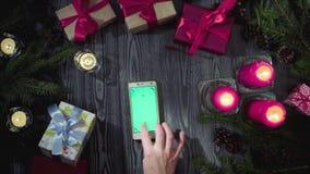 Manos femeninas que enrollan el teléfono elegante con la pantalla verde metrajes