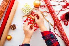 Manos femeninas que envuelven los regalos de Navidad en el papel y que los atan encima de los wi Fotos de archivo libres de regalías