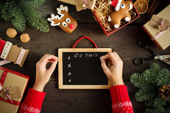 Manos femeninas que escriben el list d'envie cerca de los regalos de la Navidad Tarjeta de Navidad festiva con la pizarra Todavía Fotografía de archivo libre de regalías