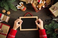 Manos femeninas que escriben el list d'envie cerca de los regalos de la Navidad Tarjeta de Navidad festiva con la pizarra Todavía Fotos de archivo libres de regalías