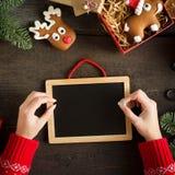 Manos femeninas que escriben el list d'envie cerca de los regalos de la Navidad Tarjeta de Navidad festiva con la pizarra Todavía Fotografía de archivo