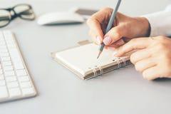 Manos femeninas que escriben en cuaderno fotografía de archivo libre de regalías