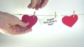 Manos femeninas que fijan tres corazones de papel rojos en un cordón con las pinzas cerca de un corazón blanco con la enhorabuena metrajes