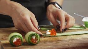 Manos femeninas que hacen el rollo del bocado del queso y del pepino del caviar almacen de video