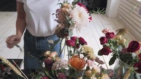 Manos femeninas que hacen la composición hermosa de la flor en tienda floral almacen de video