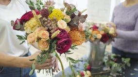 Manos femeninas que hacen la composición hermosa de la flor en tienda floral metrajes