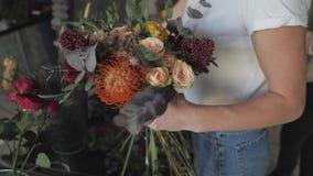 Manos femeninas que hacen la composición hermosa de la flor en tienda floral almacen de metraje de vídeo
