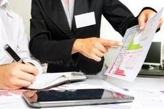 Manos femeninas que hacen la investigación en el escritorio de oficina, durante la reunión de negocios Imagen de archivo