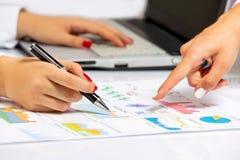 Manos femeninas que hacen la investigación sobre el escritorio de oficina, en la reunión de negocios Imagen de archivo libre de regalías