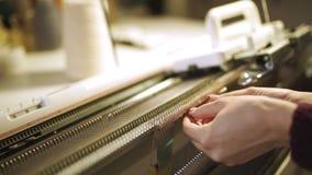 Manos femeninas que hacen la tela hecha punto en el telar en taller almacen de video