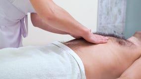 Manos femeninas que hacen masaje de relajación en el abdomen del cliente masculino en salón del balneario metrajes