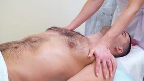 Manos femeninas que hacen masaje de relajación en hombros y pecho del paciente masculino almacen de metraje de vídeo