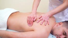 Manos femeninas que hacen masaje de relajación en la parte superior de la espalda del cliente masculino en salón del balneario metrajes