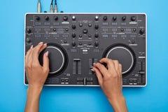 Manos femeninas que juegan el mezclador de DJ en fondo azul imagen de archivo