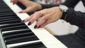 Manos femeninas que juegan el sintetizador Ciérrese para arriba con los fingeres y la mujer irreconocible que tocan los teclados  almacen de video