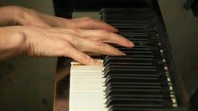 Manos femeninas que juegan un pedazo apacible de música clásica en un piano de cola hermoso Mujer que juega el piano, primer almacen de video