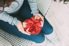 Manos femeninas que llevan a cabo el corazón de la caja de regalo Fotos de archivo