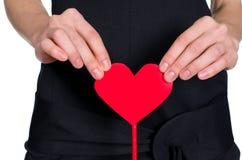 Manos femeninas que llevan a cabo el corazón fuera de pape imagenes de archivo