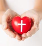Manos femeninas que llevan a cabo el corazón con símbolo cruzado Foto de archivo