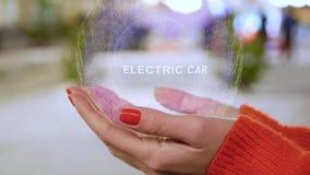 Manos femeninas que llevan a cabo el holograma con el coche eléctrico del texto almacen de video
