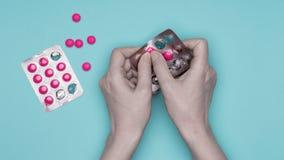 Manos femeninas que llevan a cabo el paquete de ampolla con las píldoras rosadas sobre fondo azul en colores pastel Medicación qu Foto de archivo