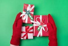 Manos femeninas que llevan a cabo la Navidad Fifts en fondo verde rojo puesto plano rojo de la opinión superior del fondo de la t fotos de archivo